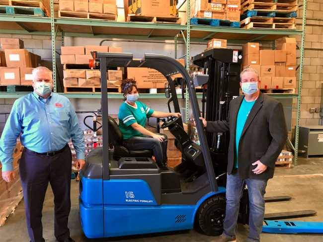 BYD and food bank employees in warehouse with a BYD forklift