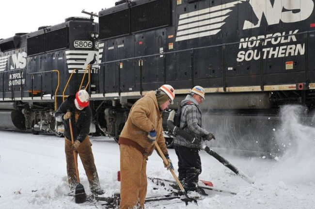 Workers clearing snow from train tracks