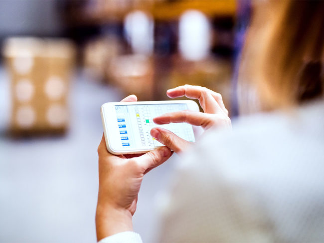 Person using handheld device in warehouse