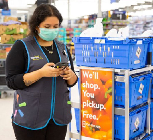 Walmart employee using mobile device in store