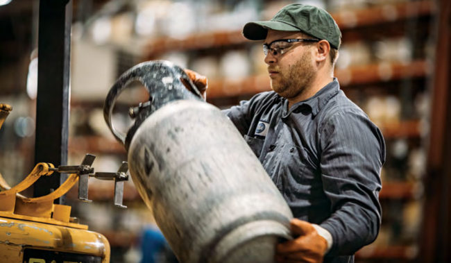 Worker handling propane tank