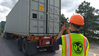 Man taking photo of container