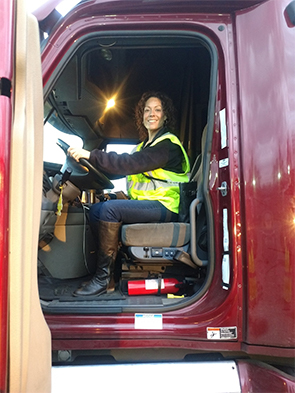 Woman sitting in semi-truck cab
