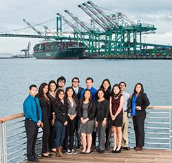 Students standing in front of ocean, cranes