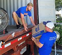 Two men loading trailer