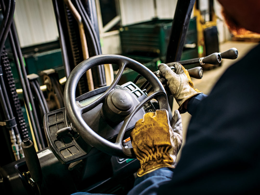 Person wearing gloves at wheel of forklift
