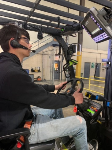 Person driving lift truck with voice headset