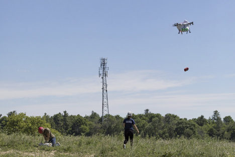 Drone making a delivery to people in a field