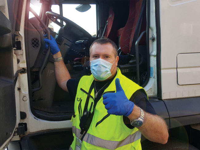 Truck driver wearing mask next to truck giving thumbs-up signal