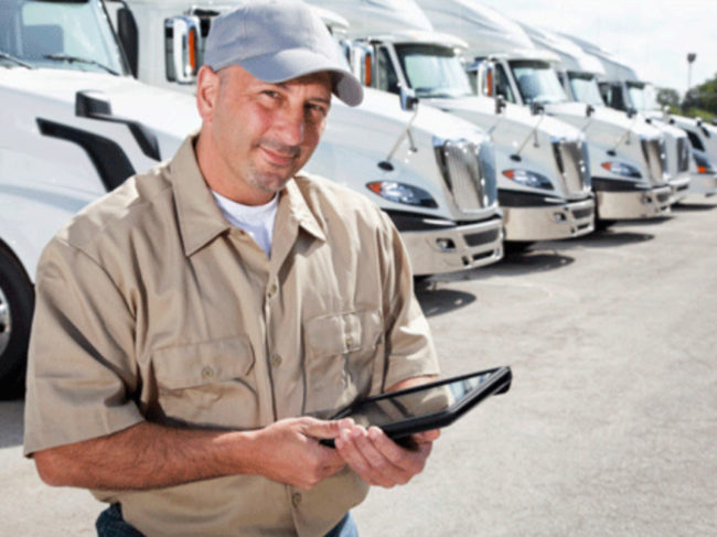 Truck driver in front of line of trucks