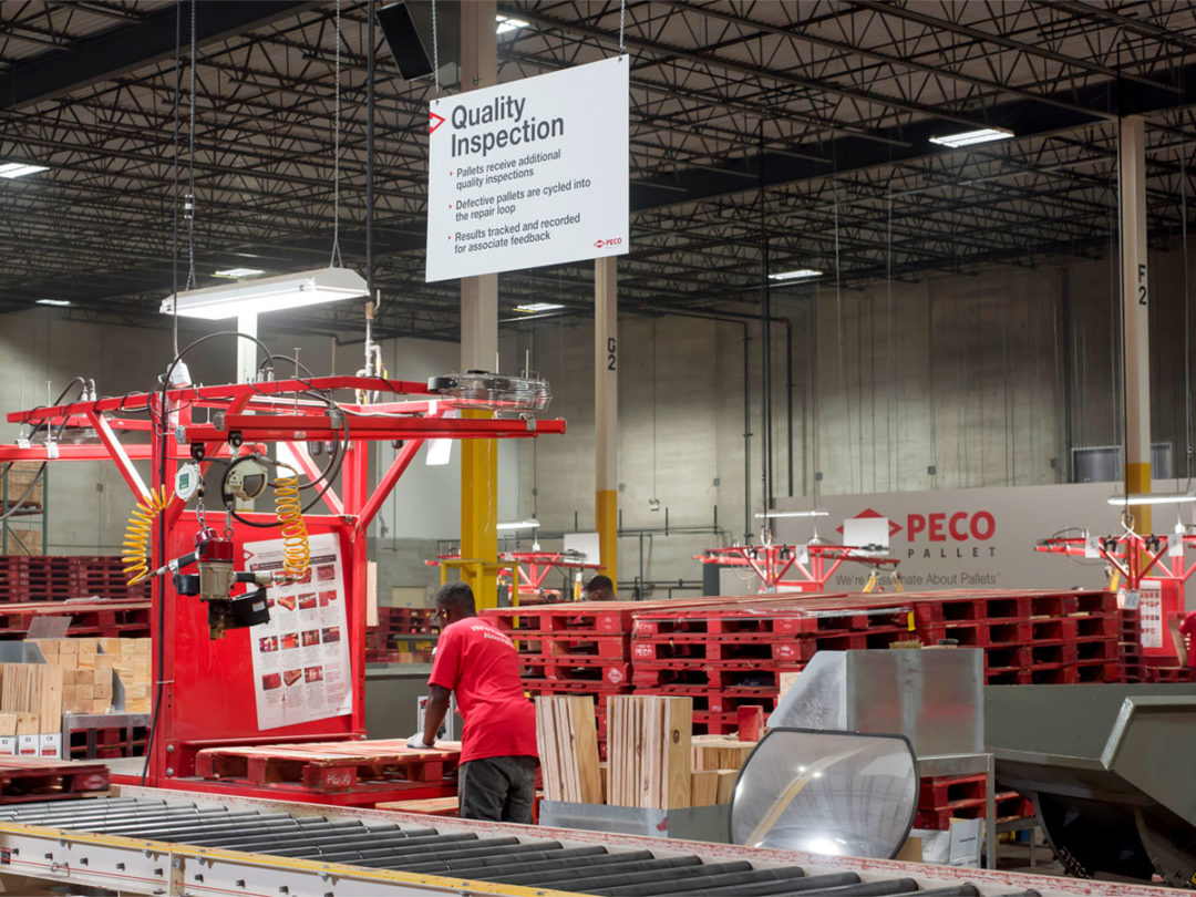Person in warehouse with PECO pallets